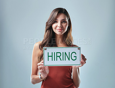 Buy stock photo Studio shot of a young woman holding up a hiring sign against a grey background