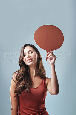 Buy stock photo Studio shot of a young woman holding up a speech bubble against a grey background