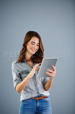 Buy stock photo Studio shot of an attractive young woman using her digital tablet against a grey background