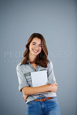Buy stock photo Studio portrait of an attractive young woman standing with a digital tablet against a grey background