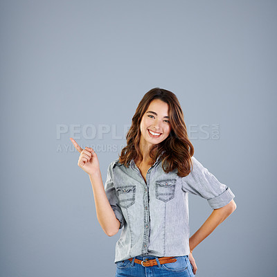 Buy stock photo Studio portrait of an attractive young woman pointing towards copyspace against a grey background