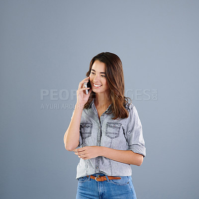 Buy stock photo Studio shot of an attractive young woman making a phonecall against a grey background