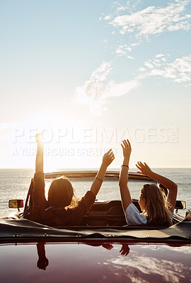 Buy stock photo Shot of a two happy young women enjoying a summer's road trip together