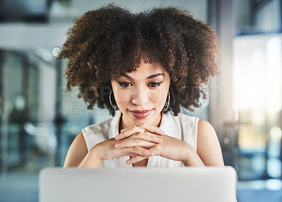 Buy stock photo Cropped shot of a cheerful young businesswoman seated at her desk and working on her laptop in the office during the day