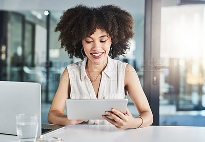 Buy stock photo Cropped shot of a cheerful young businesswoman seated at her desk and working on her digital tablet in the office during the day