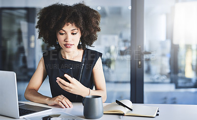 Buy stock photo Shot of a beautiful young businesswoman using a cellphone while working in her office