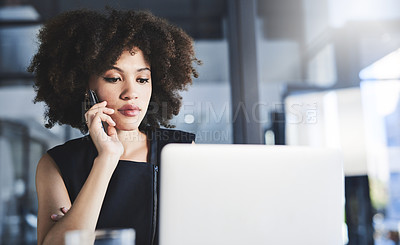 Buy stock photo Shot of a beautiful young businesswoman taking a phone call while using a laptop in her office