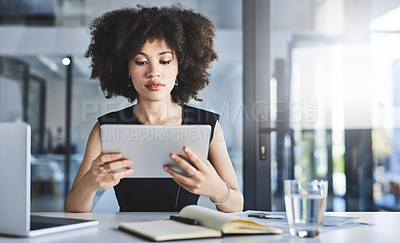 Buy stock photo Shot of a beautiful young businesswoman using a digital tablet while working in her office