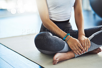 Buy stock photo Shot of an unrecognizable young woman practicing yoga while being seated on the floor inside of a yoga studio during the day