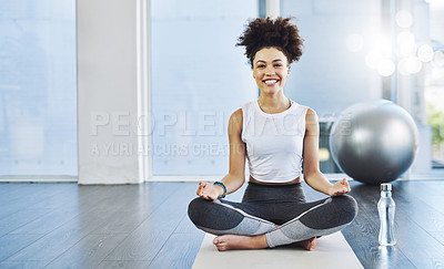 Buy stock photo Shot of a cheerful young woman practicing yoga while being seated on the floor inside of a yoga studio during the day
