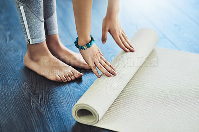 Buy stock photo Shot of an unrecognizable woman rolling down her yoga mat to do yoga exercises inside of a studio during the day