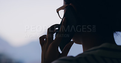 Buy stock photo Silhouetted shot of a young businesswoman making a phone call outdoors