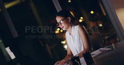 Buy stock photo Shot of a beautiful young businesswoman using a computer while working late in her office
