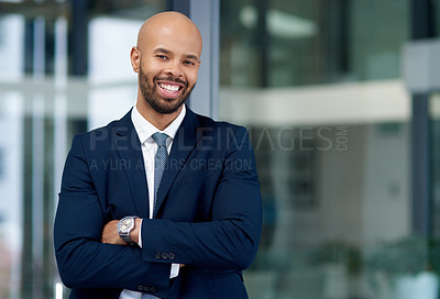 Buy stock photo Portrait of a handsome young businessman posing with his arms folded in his office