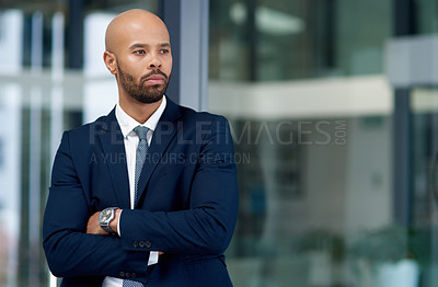 Buy stock photo Shot of a handsome young businessman posing with his arms folded in his office