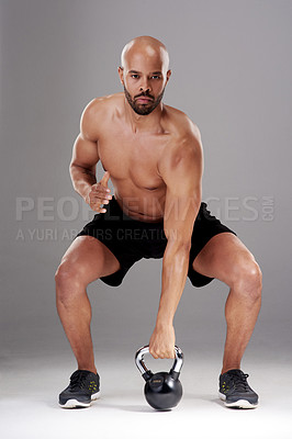 Buy stock photo Full length shot of a handsome young athlete working out with a kettlebell against a grey background