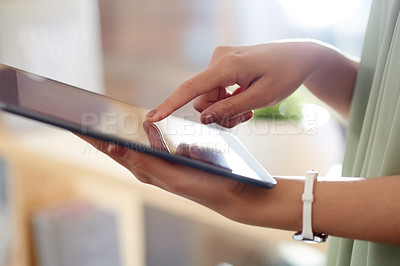 Buy stock photo Cropped shot of an unrecognizable businesswoman using her digital tablet while working in the office