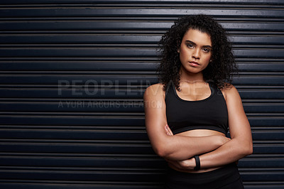 Buy stock photo Studio portrait of an attractive and athletic young woman standing with her arms crossed against a dark background