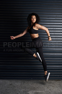 Buy stock photo Studio shot of an attractive and athletic young woman posing against a dark background
