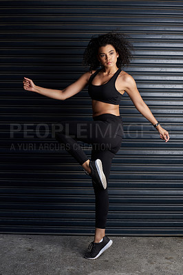 Buy stock photo Studio portrait of an attractive and athletic young woman posing against a dark background