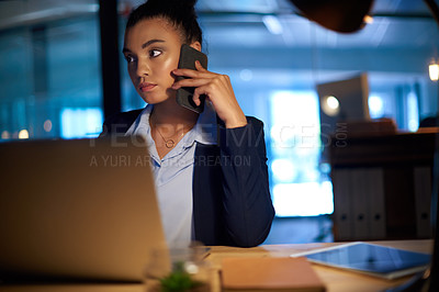 Buy stock photo Shot of a young businesswoman talking on a cellphone while working on a laptop in an office at night