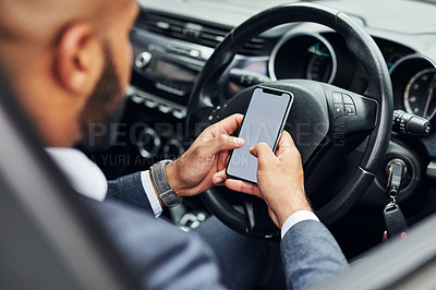 Buy stock photo Shot of an unrecognizable man using his cellphone while sitting in his car