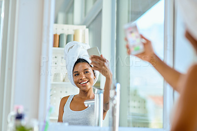 Buy stock photo Shot of an attractive young woman taking a selfie with a smartphone during her morning beauty routine
