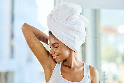 Buy stock photo Shot of an attractive young woman smelling her armpit during her morning beauty routine