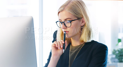 Buy stock photo Cropped shot of a focused young businesswoman working on her computer while contemplating inside of the office