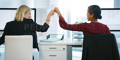 Buy stock photo Rearview shot of two young businesswomen pounding their fists in succession while being seated at their desk in the office