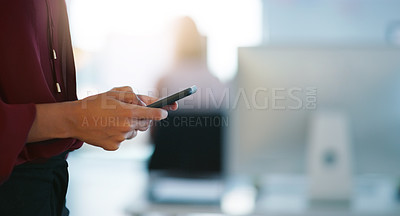 Buy stock photo Cropped shot of an unrecognizable businesswoman texting on her cellphone inside of the office during the day