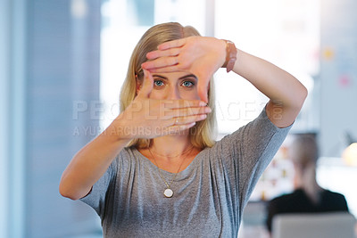 Buy stock photo Portrait of a confident young businesswoman making a frame with her hands and looking through it inside of the office