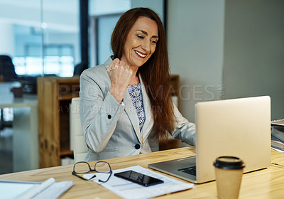 Buy stock photo Shot of a mature businesswoman cheering while working on a laptop in an office at night