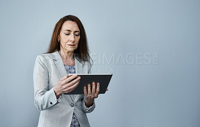 Buy stock photo Studio shot of a mature businesswoman using a digital tablet against a grey background