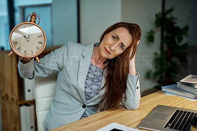 Buy stock photo Portrait of a mature businesswoman holding a clock and looking stressed out while working late in an office