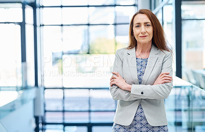 Buy stock photo Portrait of a mature businesswoman standing with her arms crossed in an office