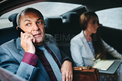 Buy stock photo Shot of a mature businessman talking on a cellphone while travelling with a colleague in a car