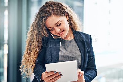 Buy stock photo Shot of a young businesswoman using a digital tablet while talking on a cellphone in an office
