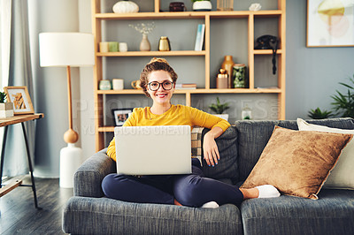 Buy stock photo Portrait of a happy young woman using a laptop on the sofa at home
