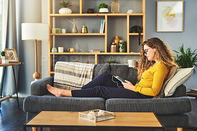 Buy stock photo Shot of a young woman using a digital tablet and earphones while having coffee on the sofa at home