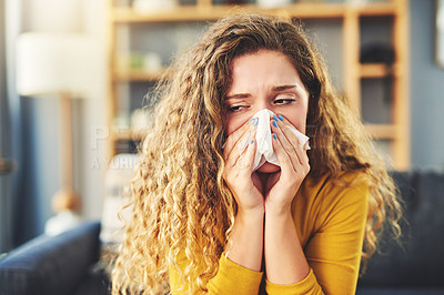 Buy stock photo Shot of a young woman blowing her nose with a tissue at home