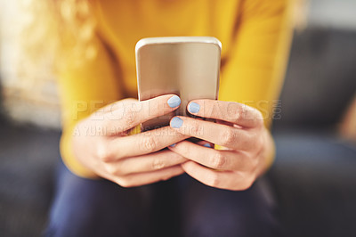 Buy stock photo Cropped shot of an unrecognizable woman using a smartphone on the sofa at home