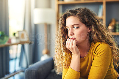 Buy stock photo Shot of a young woman looking depressed at home