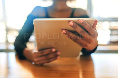 Buy stock photo Cropped shot of an unrecognizable woman browsing on a digital tablet inside at home during the day
