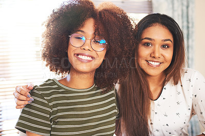 Buy stock photo Portrait of two cheerful young friends standing together arms around while looking at the camera at home during the day