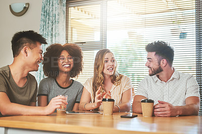 Buy stock photo Cropped shot of a group of cheerful young friends seated together while having coffee at home during the day