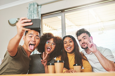 Buy stock photo Cropped shot of a group of cheerful young friends taking a self portrait together inside at home during the day