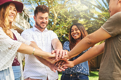 Buy stock photo Cropped shot of a group of cheerful young friends making a huddle with their hands outside during the day