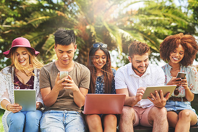 Buy stock photo Cropped shot of a carefree young group of friends browsing on their digital devices together outside during the day