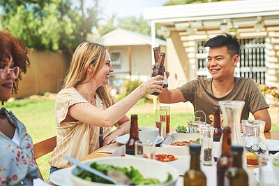 Buy stock photo Cropped shot of two cheerful young friends having a celebratory toast with drinks while being seated at a lunch table with friends